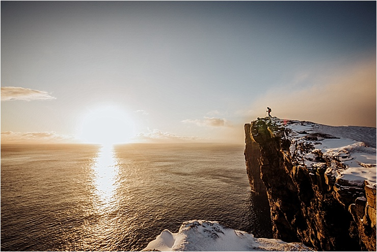 Standing on a cliff watching the sunrise in the Faroe Islands by We Are The Wanderers