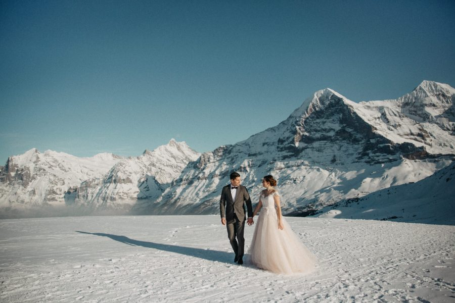 Winter wedding in the mountains couple walking across the snow by Delia Folghera Photography