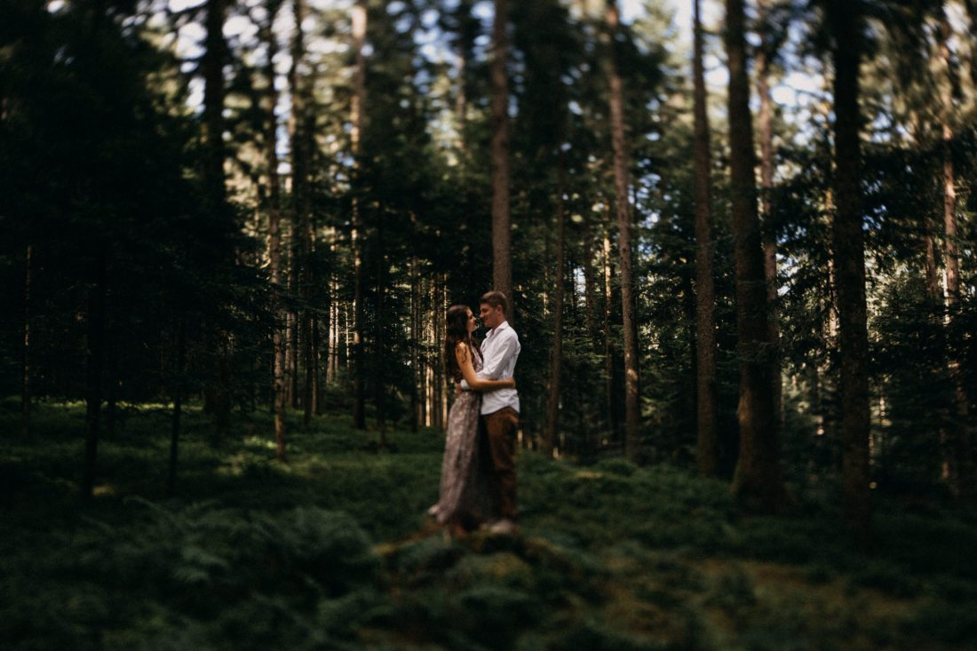 Couple embrace in a forest by Delia Folghera Photography