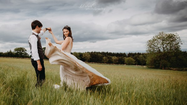 Groom twirls his bride in a field of long grass in the English countryside as her dress blows in the wind by Unfurl Photography