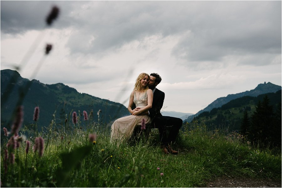 Bride and groom find a wooden bench in a meadow - After wedding honeymoon shoot in Wengen by Caroline Hancox Photography