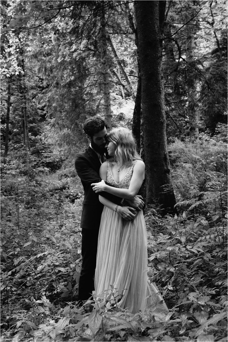 The groom embraces his bride in a forest - After wedding honeymoon shoot in Wengen by Caroline Hancox Photography