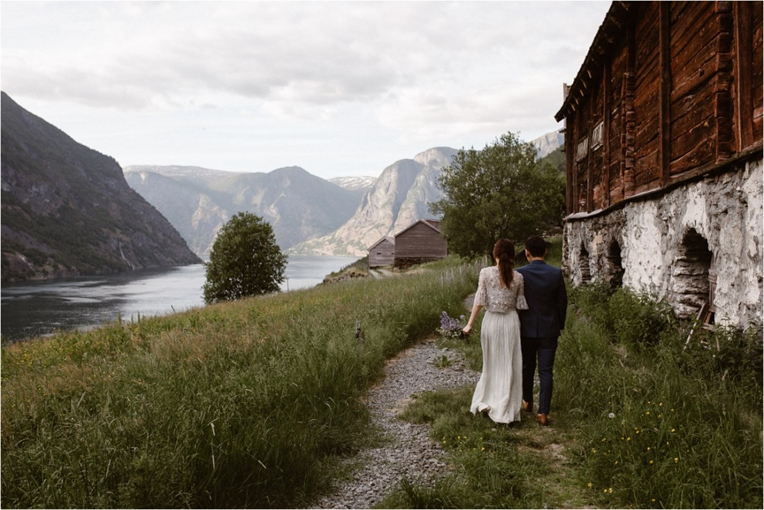 Bride & groom walk along side some old farm houses in Norway by Ingvild Kolnes