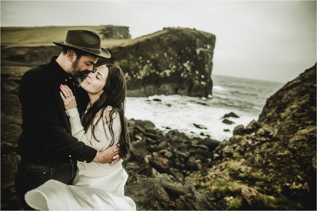Gaby & German embrace in front of the cliffs of the Reykjanes peninsula for their Iceland anniversary shoot by Projectphoto.ch