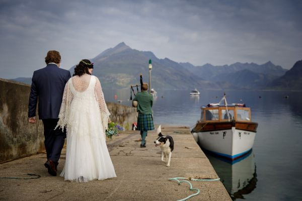 Tina & Jürgen walk to the boat for their Loch Coruisak Elopement on the Isle of Skye by Lynne Kennedy Photography