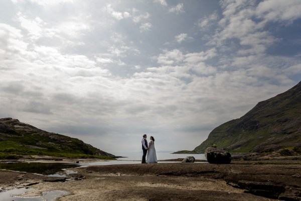 Tina & Jürgen stand on the banks of the Loch after their elopement ceremony by Lynne Kennedy Photography