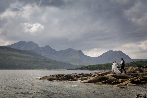Tina helps Jürgen across the rocks by the Loch after their elopement Black & white image of Tina & Jürgen embracing on some rocks by the shores of the Loch by Lynne Kennedy Photography