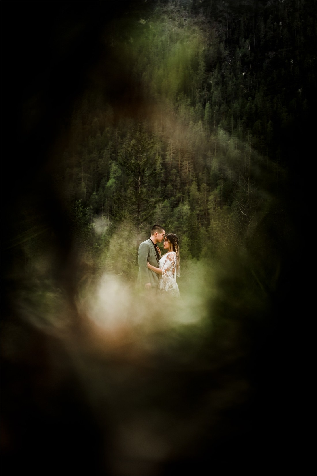 A picture of Christina & Ted through the branches of the trees in the Dolomites forest by Wild Connections Photography