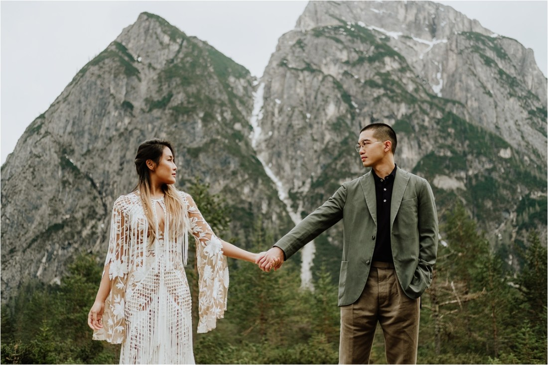 Christina & Ted hold hands with mountains behind them by Wild Connections Photography