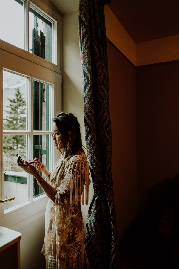 Christina uses the window light to put on her makeup at Hotel Lago Di Braies by Wild Connections Photography