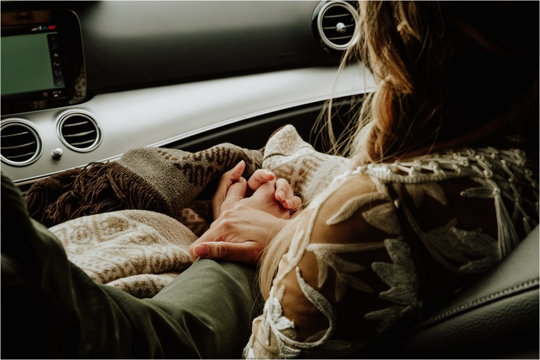 Holding hands in the car on a Dolomites road trip by Wild Connections Photography