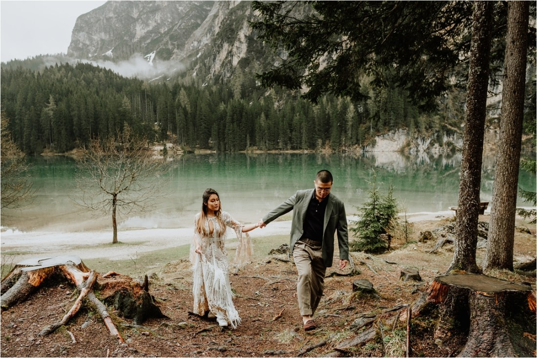 A pre-wedding shoot at Lago di Braies in the Dolomites by Wild Connections Photography couple walk in to the forest