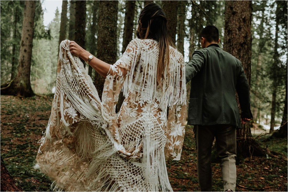 Christina holds up her Rue De Seine wedding dress as they walk through the forest by Wild Connections Photography