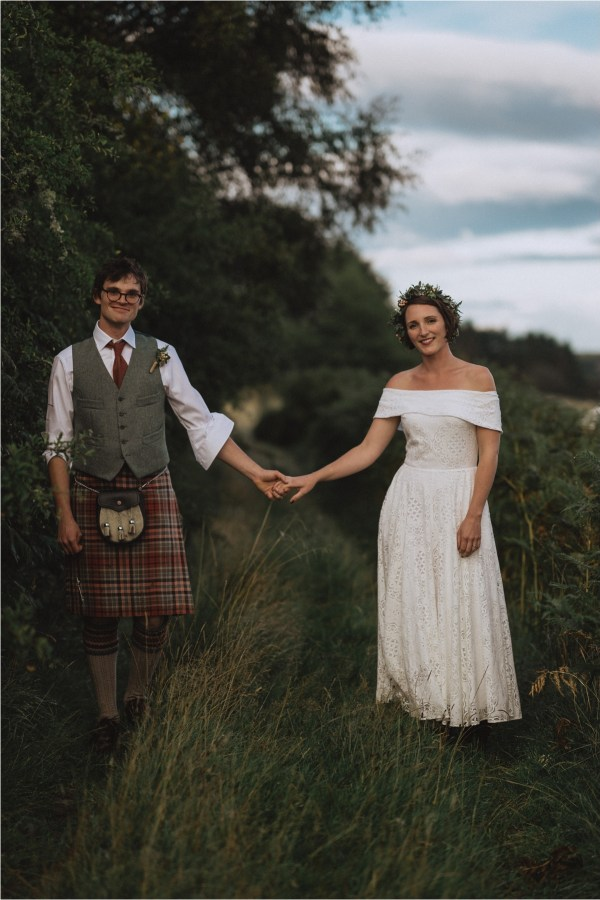 Bride & groom holiday hands in the long grass by Fox & Bear Photography