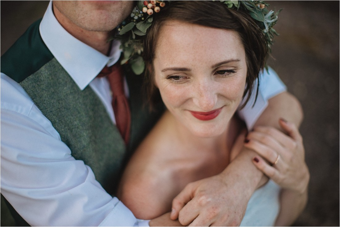 The groom embraces the bride as she smiles by Fox & Bear Photography