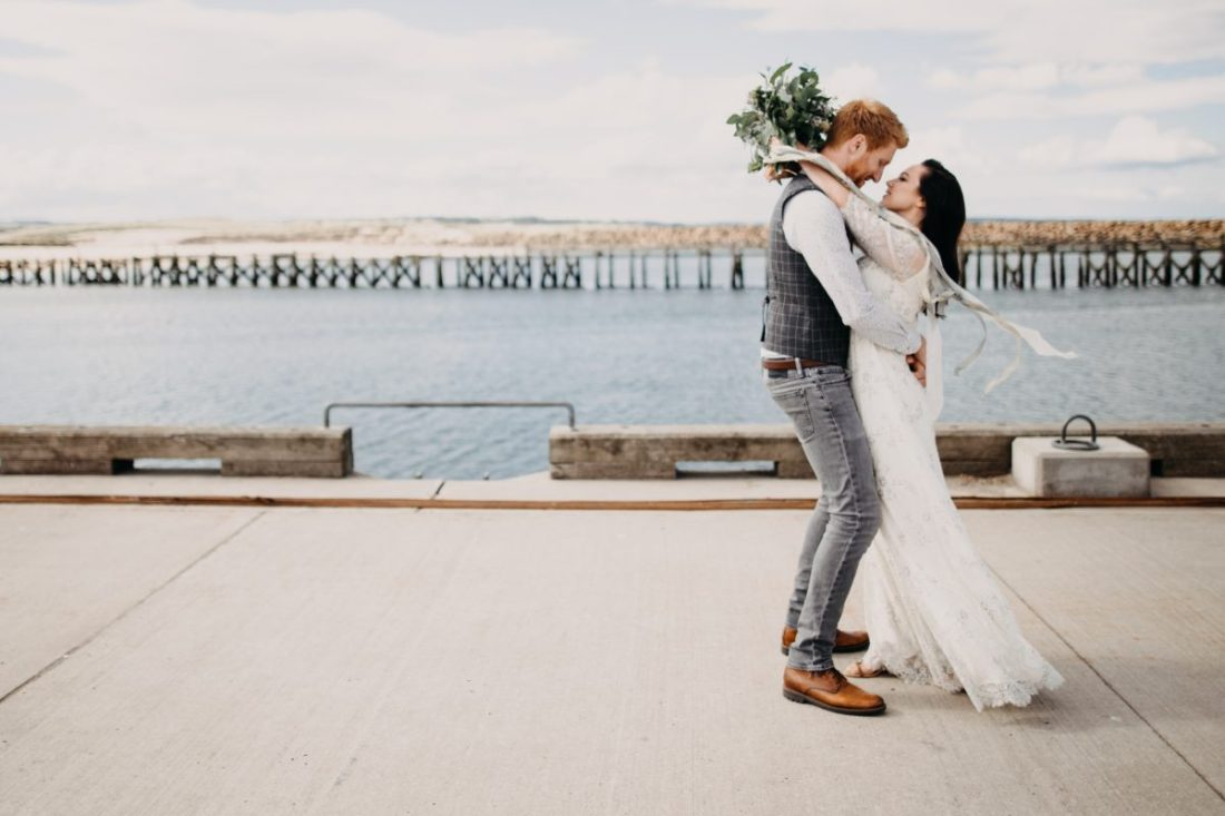 Bride and groom kissing on a pier by Unfurl Photography