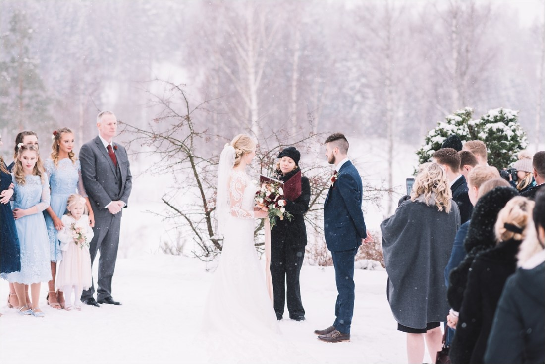The couple say their wedding vows in the snow in Finland by Lucie Watson Photography