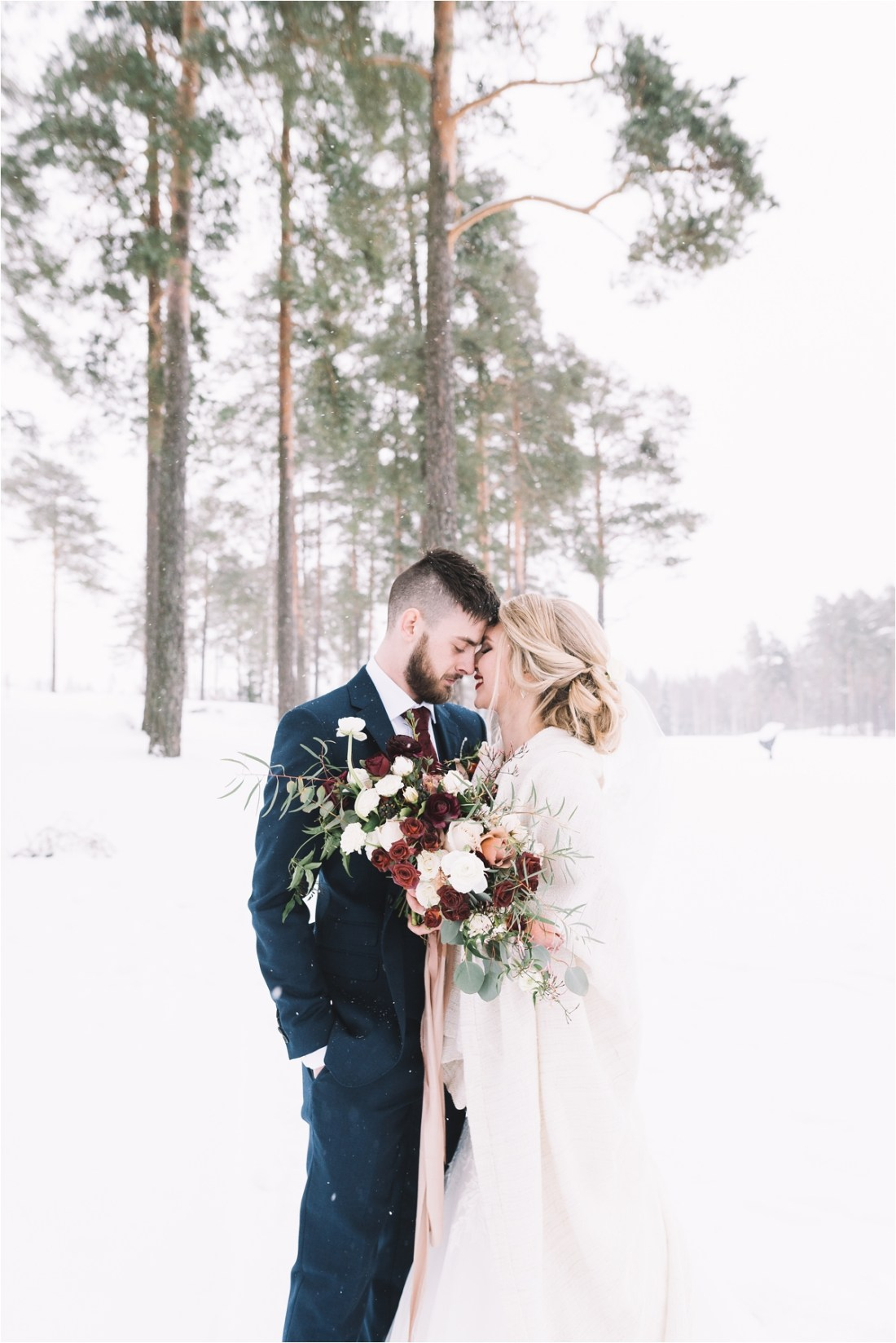 The bride and groom standing head to head in the snow by Lucie Watson Photography