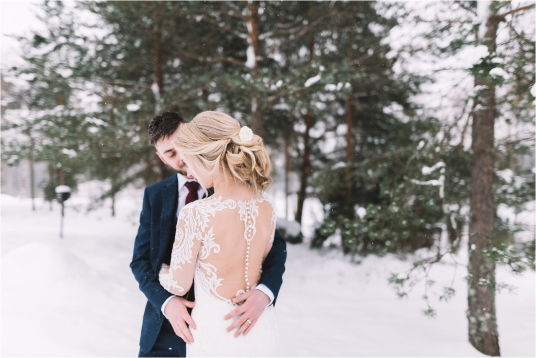 The bride and groom embrace in the snow in winter by Lucie Watson Photography