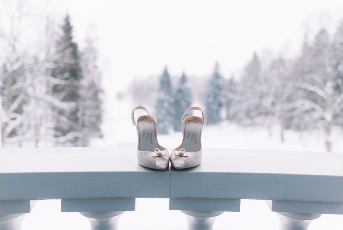 Winter wedding shoes on the hotel room balcony with a snowy backdrop