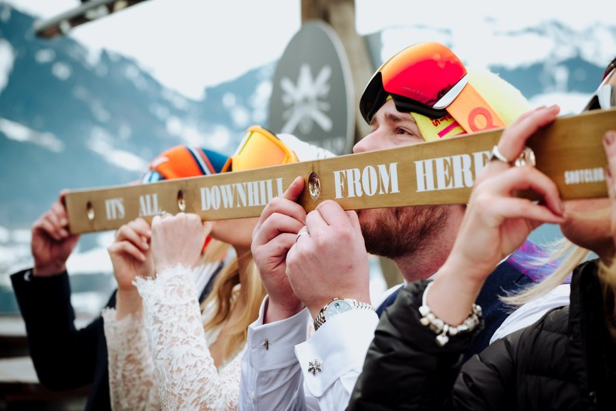 Wedding party do a shot ski at their ski wedding by Wild Connections Photography