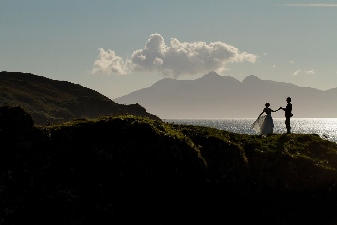 Silhouettes of a couple walking along a cliff by Lynne Kennedy Photography