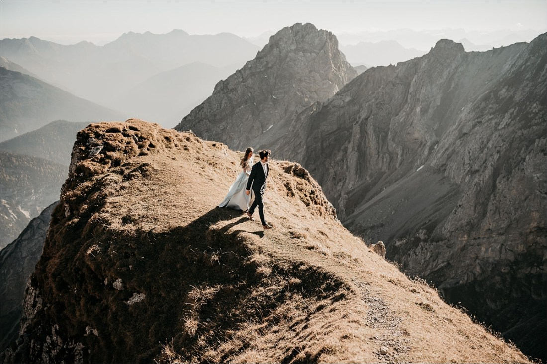 Bride and groom walking along a mountain ridge in Bavaria at sunset by Aneta Lehotska