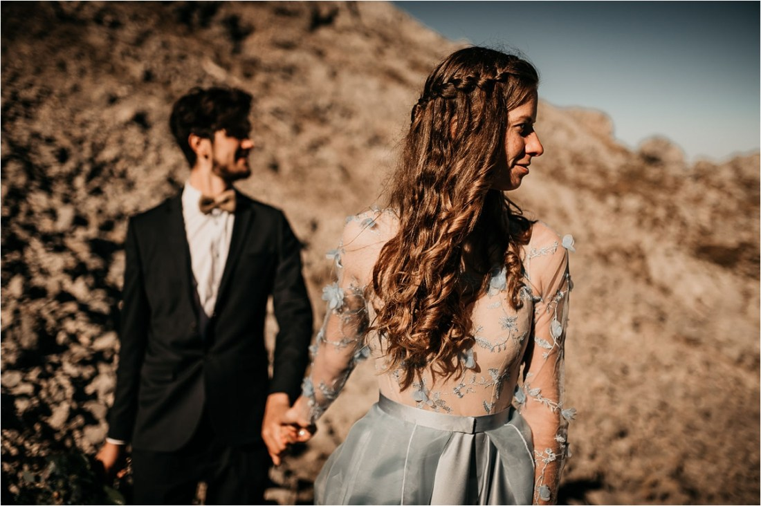 Bride and groom walk hand-in-hand towards the camera on a mountain by Aneta Lehotska