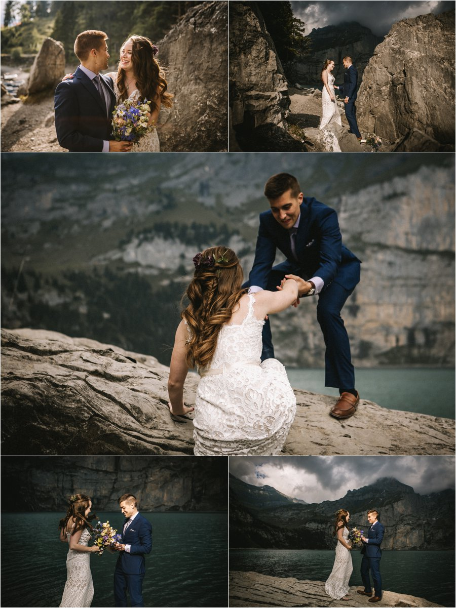 The groom helps the bride on to a rock by a lake in the Swiss Alps for their elopement ceremony by Bendik Photography