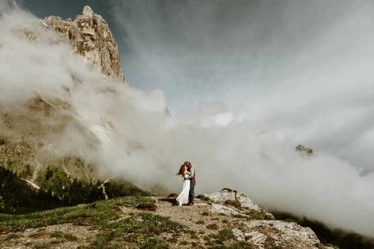 Bride and groom embrace as the wind blows the wedding dress by Wild Connections Photography