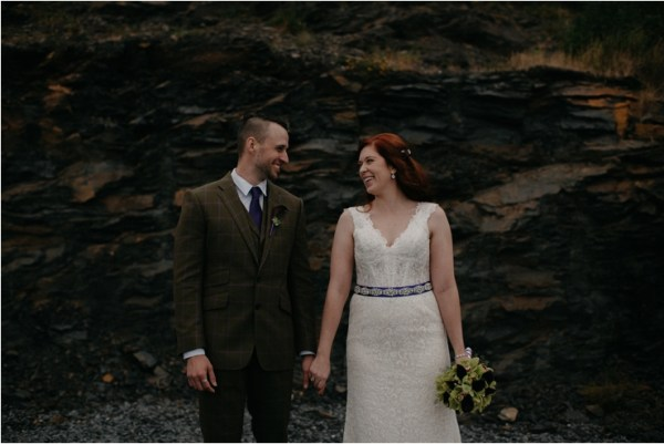 Cliff top Hand fasting of Jon and Sara, on the Cliffs of Moher, Co Clare, Ireland Captured by Photographers Seandkate a portraits of the bride and groom holding hands and looking at each other in front of a black stone wall