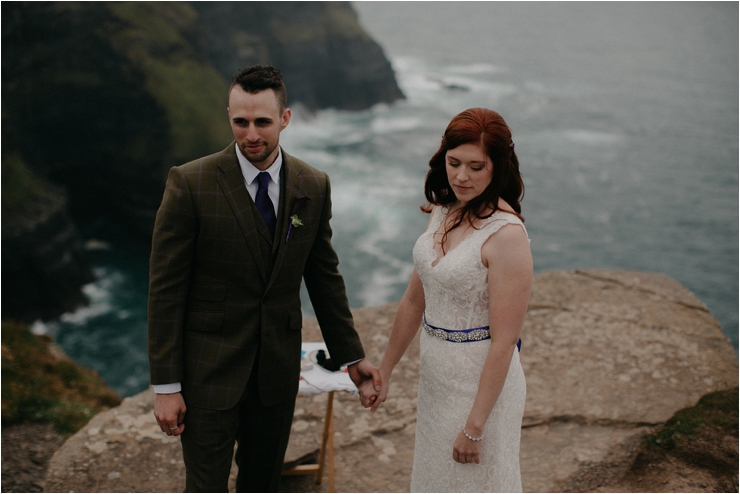 Cliff top Hand fasting of Jon and Sara, on the Cliffs of Moher, Co Clare, Ireland Captured by Photographers Seandkate the couple hold hands on the clifftop during their ceremony