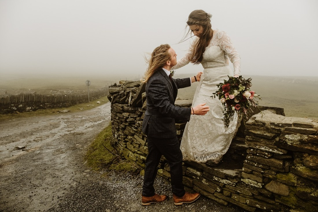 Bride climbs over a stone wall on the way to her elopement at the Cliffs of Moher in Ireland