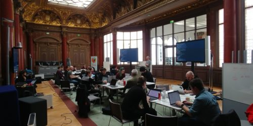 People clustered around 3 desks working on their computers in a beautiful 19th century Parisian ballroom. inch width=