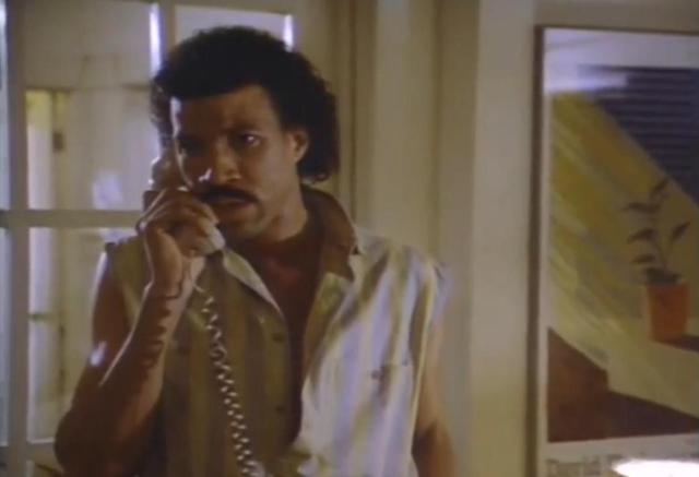 "Lionel Richie answering an 80's telephone through the video for "" Hello"" inch width="