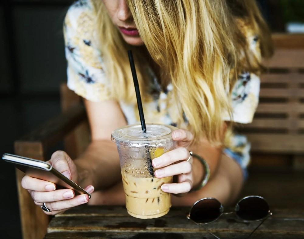 カップとスマートフォンを持つ女の子