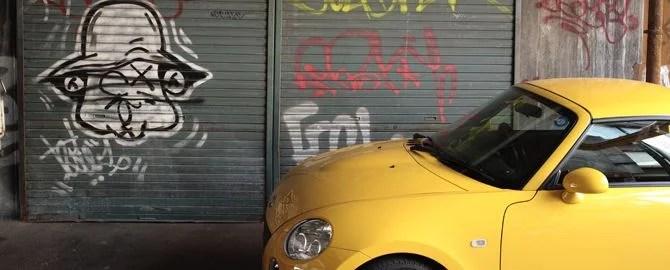 壁の落書きと黄色い車