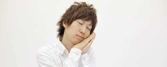 睡眠の仕草をする男性