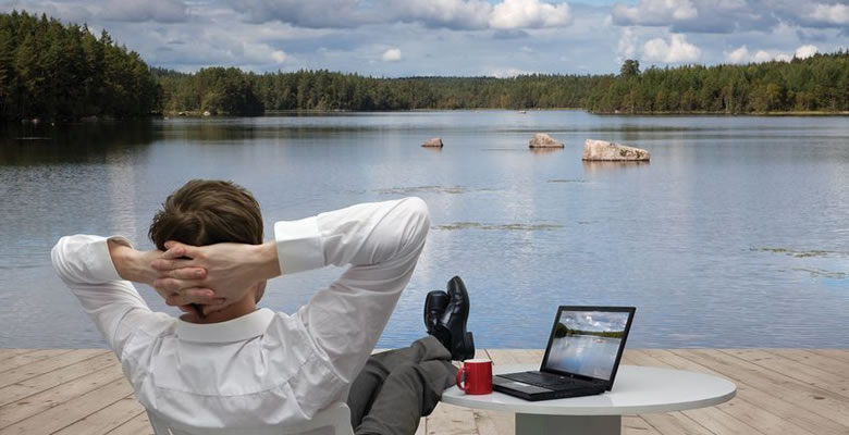 Man with laptop relaxing by lake