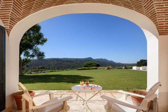 Espace ouvert voûté avec 2 chaises donnant sur un paysage verdoyant et à flanc de colline.