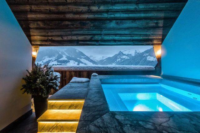 Piscine thermale avec fenêtre donnant sur les Alpes suisses en hiver