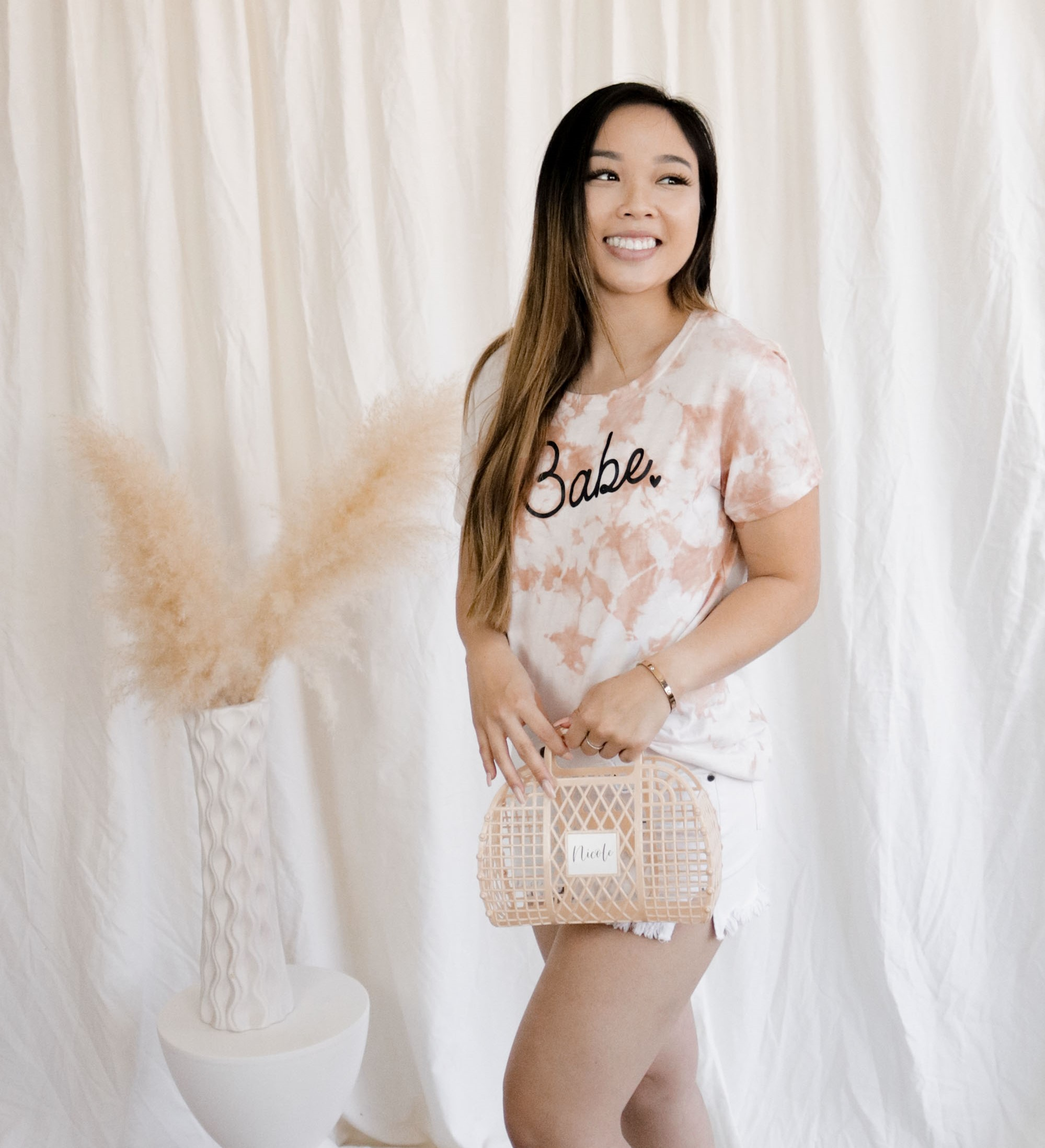 Girl wearing finished DIY tie dye shirt with Babe printed on the front. She is also wearing white shorts and holding a beige jelly bag with the name Nicole on the front