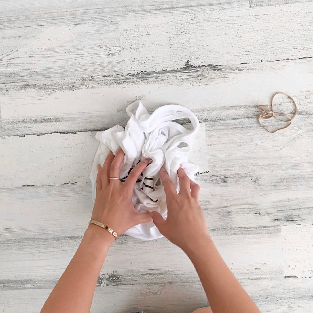 Girl scrunching a white shirt before she gets ready to secure it with rubber bands