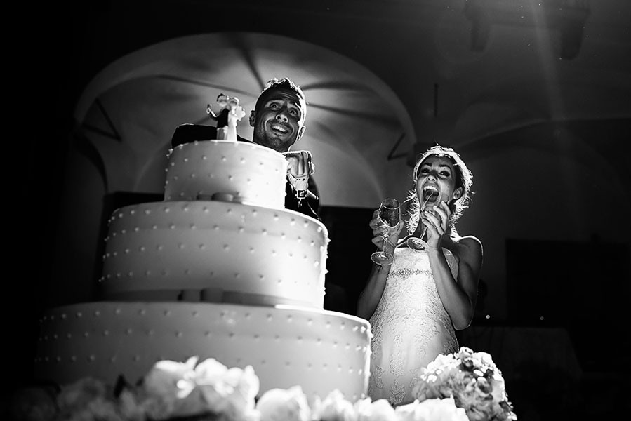 Newly married couple about to cut their wedding cake
