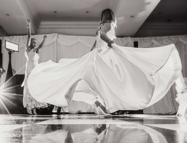 Bride jumping on the bed in wedding dress