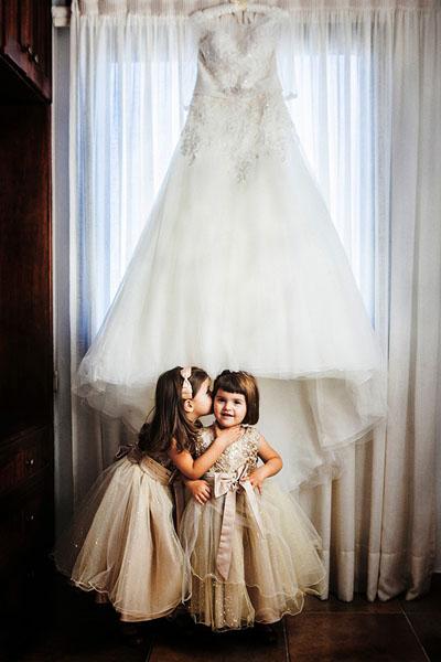 flower girls cuddling under wedding dress