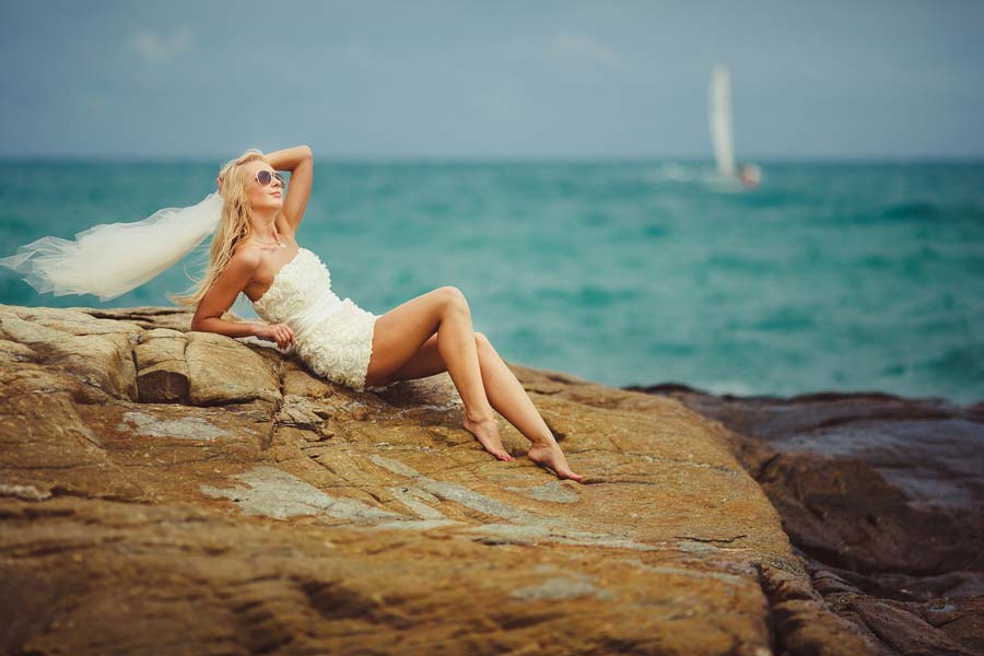 Bride In Short Wedding Dress On The Rocky Beach. Young Beautiful