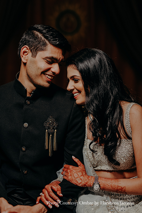 bride in silver embroidery sangeet lehenga and groom in black velvet bandhgala and black trousers