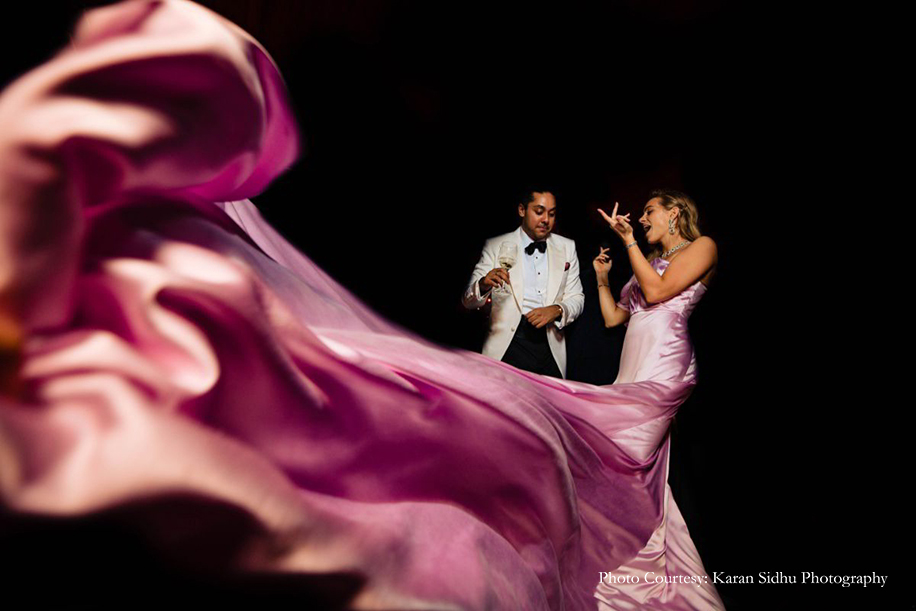 Bride in pink gown and groom in black and white tuxedo for sangeet