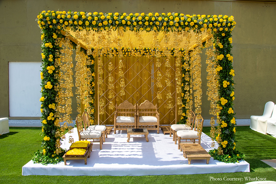 mandap decor with yellow drapes, lots of greens, fresh marigolds, and gold kalires dangling from the ceiling